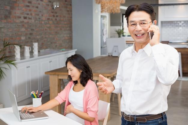 Homme souriant sur un appel téléphonique pendant que la femme enceinte utilise un ordinateur portable Photo Premium