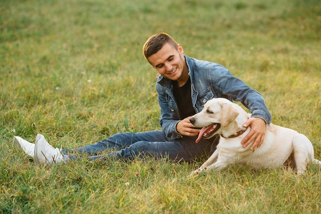 Homme souriant, assis sur l'herbe avec son chien labrador dans le parc Photo gratuit