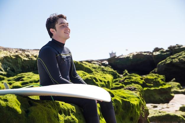 Homme souriant assis sur des rochers moussus avec planche de surf Photo gratuit