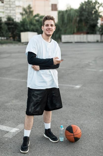 Homme souriant avec un ballon de basket Photo gratuit