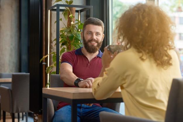 Homme souriant à la barbe en regardant la fille assise en font de lui. Photo Premium