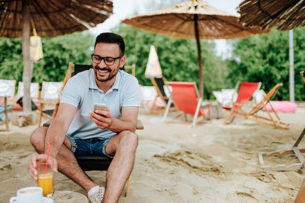 Homme souriant, buvant un cocktail à la plage et utilisant un téléphone. Photo Premium
