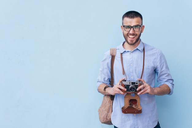Homme souriant, clin d'oeil tout en tenant la caméra debout sur fond bleu Photo gratuit