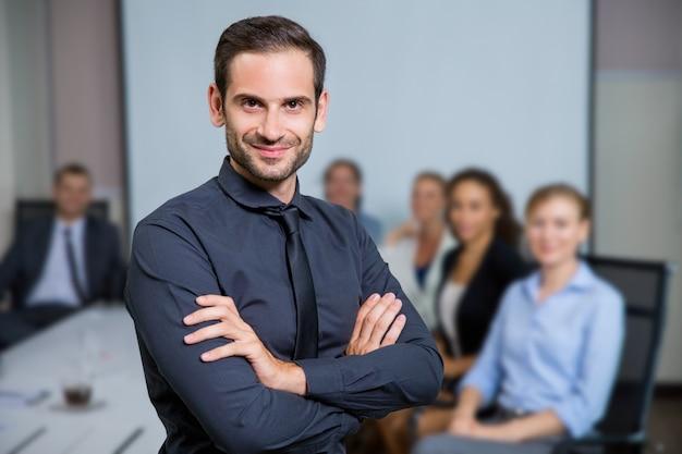 Homme Souriant homme souriant avec le costume assis à une table avec des collègues