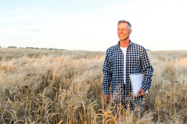 Homme souriant dans un champ de blé Photo gratuit