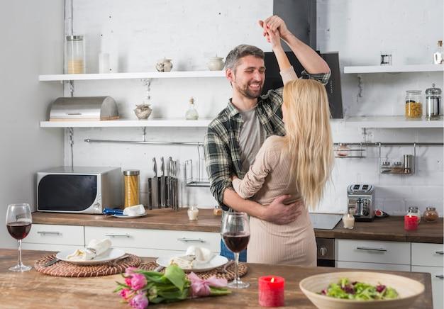 Homme souriant dansant avec une femme blonde près de la table dans la cuisine Photo gratuit