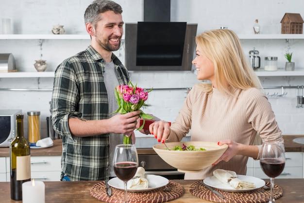 Homme souriant donnant des cadeaux et des fleurs à une femme joyeuse avec un bol dans la cuisine Photo gratuit