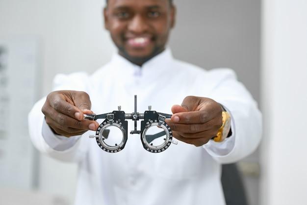 Homme souriant donnant des lentilles médicales à essayer dans le laboratoire d'ophtalmologie blanche. Photo Premium
