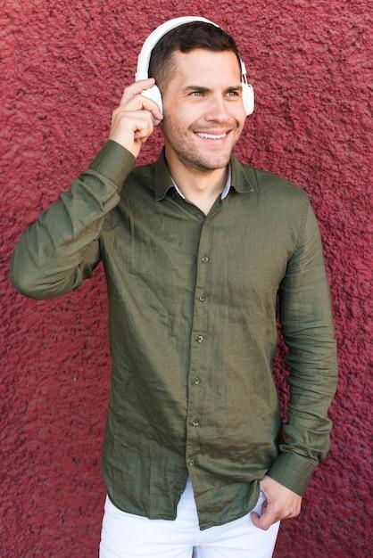 Homme souriant, écoute de la musique au casque debout près d'un mur rugueux rouge Photo gratuit