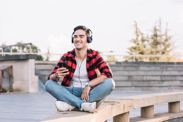 Homme souriant, écoute de la musique sur le casque Photo gratuit