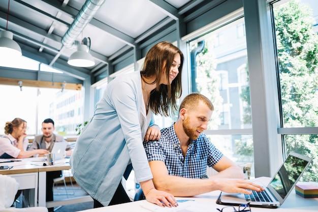 Homme Souriant Et Femme Coopérant à L'ordinateur Portable Photo gratuit