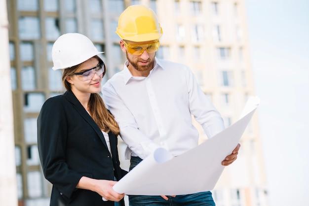 Homme souriant et femme regardant blueprint Photo gratuit