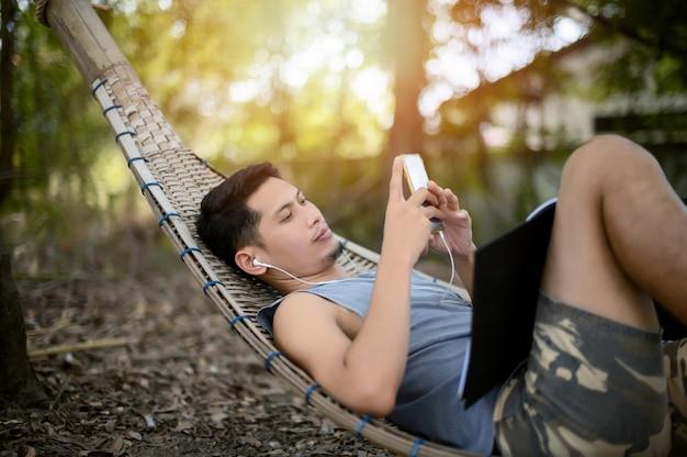 Un Homme Souriant Et Jouant Au Téléphone Sur Une Civière En Bois Dans Une Forêt. Reste à La Maison. Joyeuses Vacances. Photo Premium