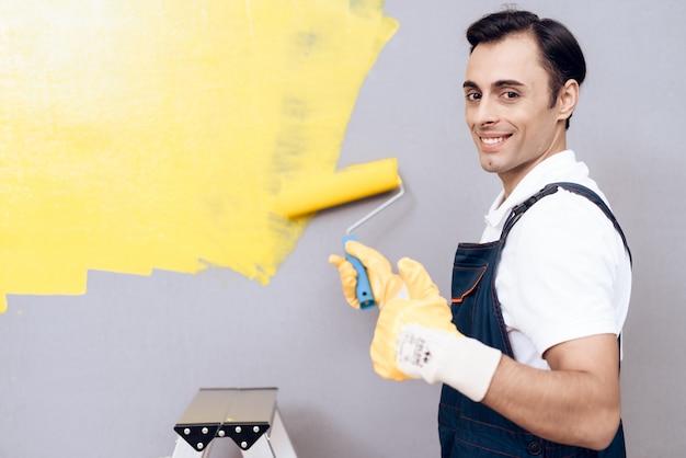 Homme souriant sur labber en peinture uniforme gris mur. Photo Premium