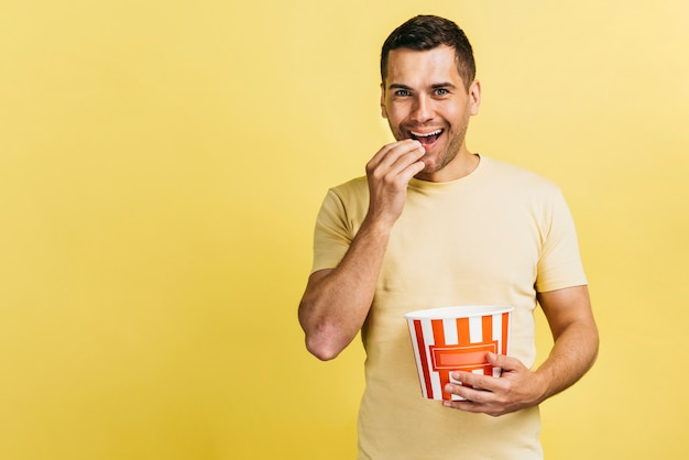Homme souriant mangeant du pop-corn Photo gratuit