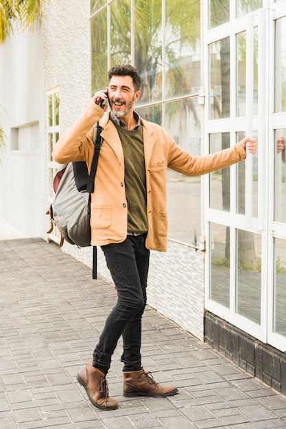 Homme souriant moderne avec son sac à dos, parler au téléphone portable tout en ouvrant la porte vitrée Photo gratuit