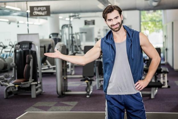 Homme souriant montrant la salle de sport à la caméra Photo Premium