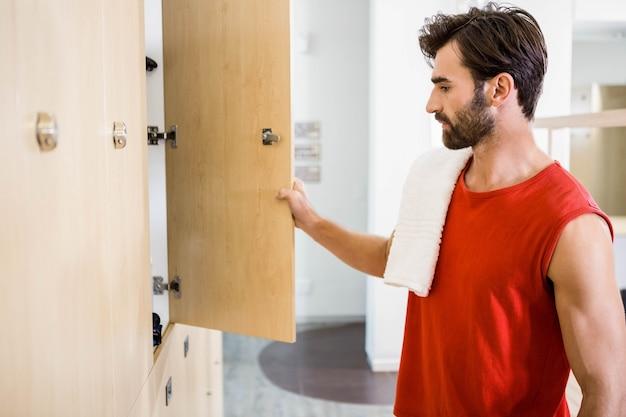 Homme souriant, ouverture casier, dans, les, gymnase Photo Premium