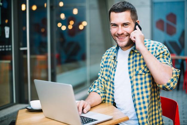 Homme souriant, posant avec des gadgets au café Photo gratuit