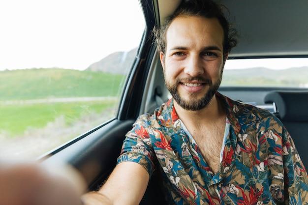 Homme souriant prenant selfie en voiture Photo gratuit
