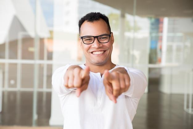Homme souriant en regardant la caméra, en montrant la caméra avec les mains Photo gratuit