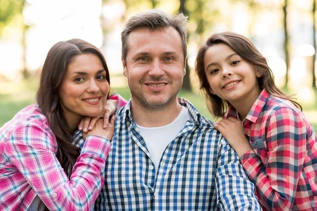 Homme souriant avec sa femme et sa fille en regardant la caméra dans le parc Photo gratuit