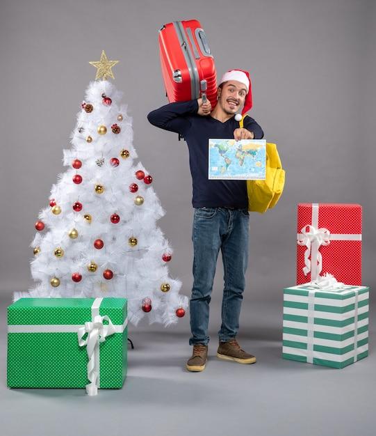 Homme Souriant Avec Sac à Dos Jaune Tenant La Carte Près De L'arbre De Noël Sur Fond Gris Photo gratuit