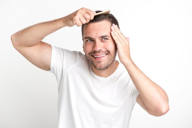 Un homme souriant en t-shirt blanc se peigne les cheveux Photo gratuit