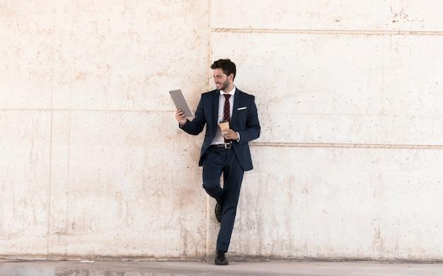 Homme souriant avec tablette et café Photo gratuit