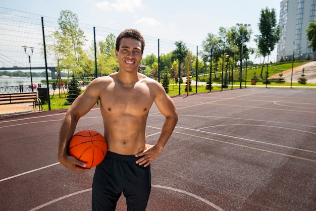 Homme souriant tenant un ballon dans un parc urbain Photo gratuit