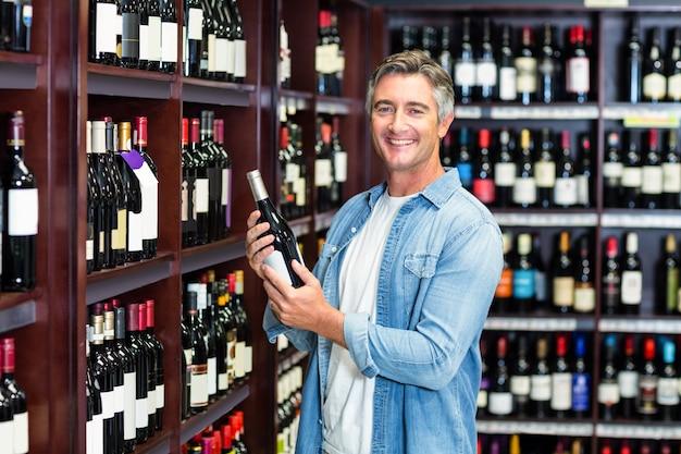 Homme souriant tenant une bouteille de vin Photo Premium