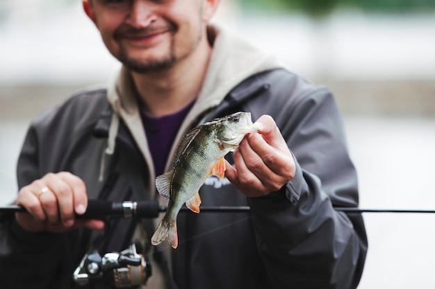 Homme souriant, tenant la canne à pêche montrant des poissons capturés Photo gratuit
