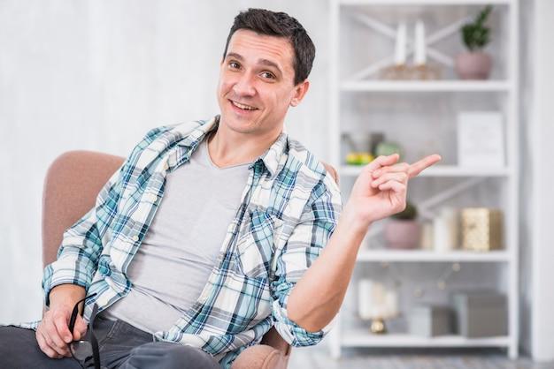 Homme souriant tenant des lunettes et pointant loin sur une chaise à la maison Photo gratuit