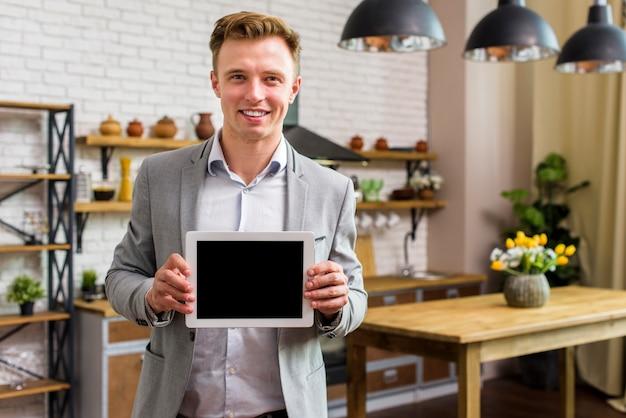 Homme souriant tenant la maquette de la tablette Photo gratuit