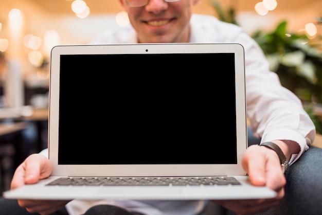 Homme souriant tenant un ordinateur portable ouvert avec écran noir Photo gratuit