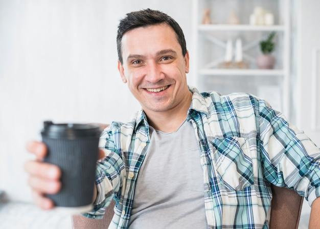 Homme souriant tenant une tasse de boisson sur une chaise à la maison Photo gratuit