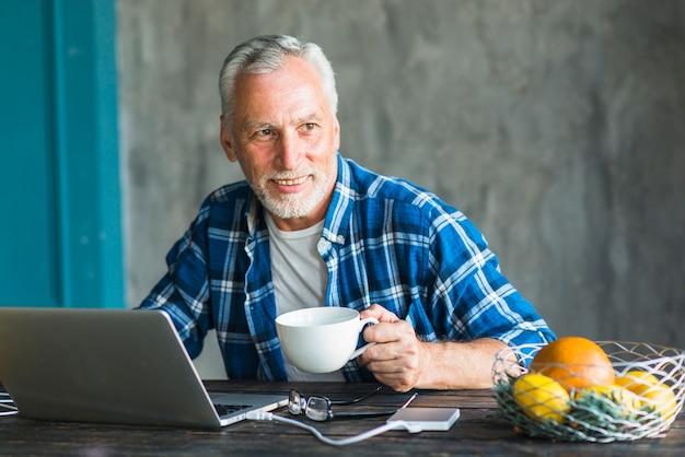 Homme souriant tenant la tasse de café en regardant loin avec ordinateur portable sur la table Photo gratuit