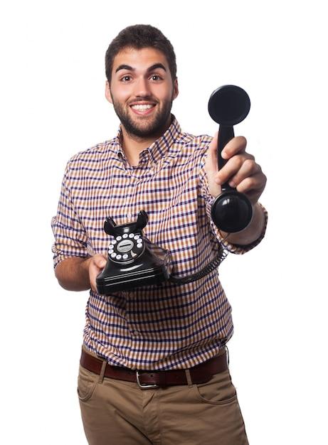 Homme Souriant Avec Un Vieux Téléphone Photo gratuit