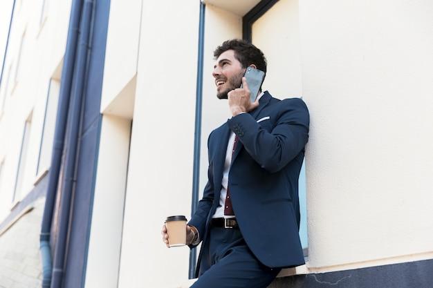 Homme souriant vue de côté, parler au téléphone Photo gratuit