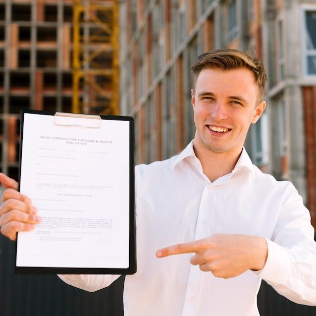 Homme souriant vue de face pointant vers le contrat Photo gratuit