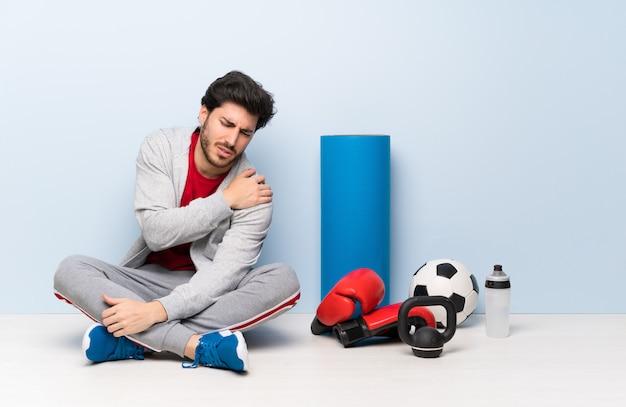 Homme de sport assis sur le sol souffrant de douleurs à l'épaule pour avoir fait un effort Photo Premium