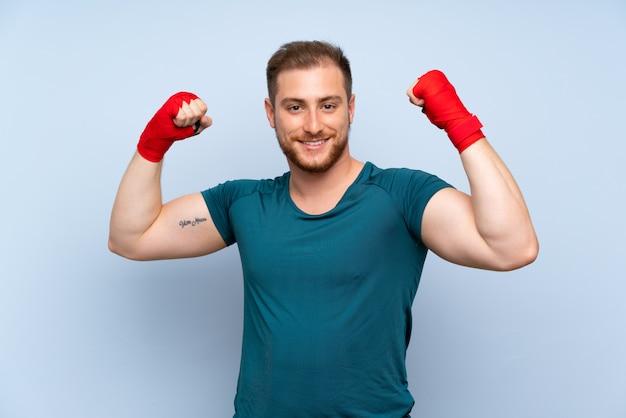 Homme de sport blonde sur un mur bleu dans des bandages de boxe Photo Premium