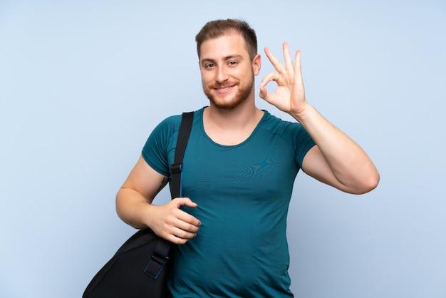 Homme de sport blonde sur mur bleu montrant signe ok avec les doigts Photo Premium