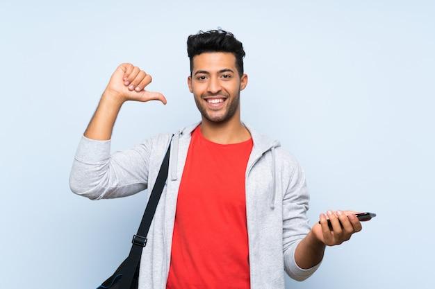 Homme de sport sur mur bleu isolé fier et satisfait Photo Premium