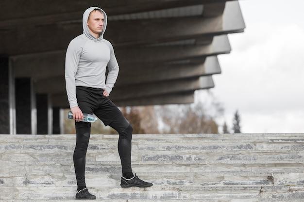 Homme sportif assis dans les escaliers et en posant la mode Photo gratuit