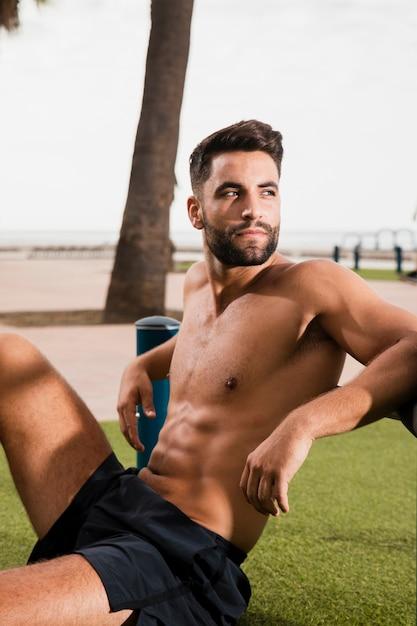 Homme sportif assis tout en regardant loin Photo gratuit