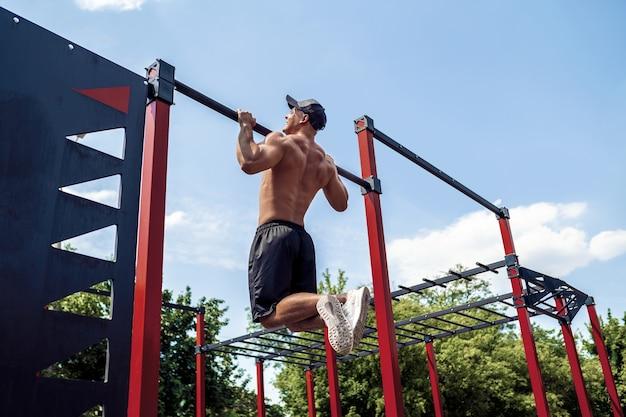 Homme sportif brutal faisant des exercices de traction sur une barre transversale. Photo Premium