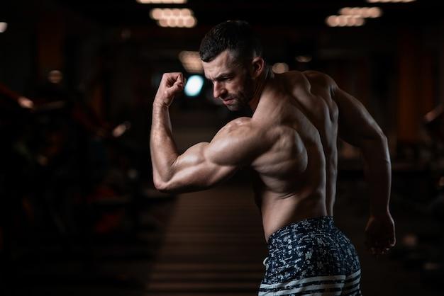 Homme sportif avec un corps musclé pose dans la salle de gym, exhibant ses biceps. le concept d'un mode de vie sain Photo Premium