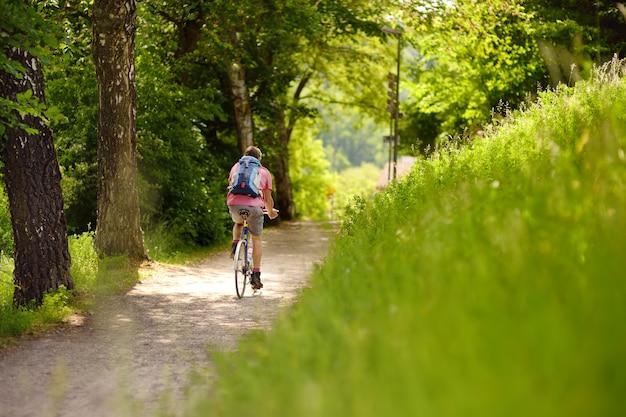 Homme sportif cyclisme dans un parc ensoleillé en chaude journée d'été. suisse, europe Photo Premium