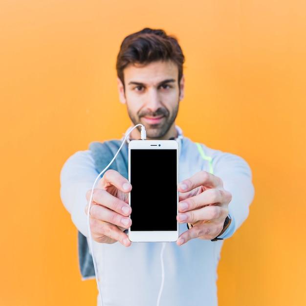 Homme sportif démontré smartphone Photo gratuit